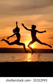 Silhouettes of happy couple jumping over seashore at sunset