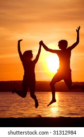 Silhouettes of happy couple jumping with raised arms near lake at sunset