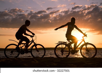 Silhouettes of happy couple riding their bicycles on seashore at sunset