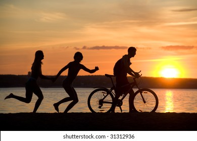 Silhouettes of happy couple running behind man riding bicycle on seashore at sunset