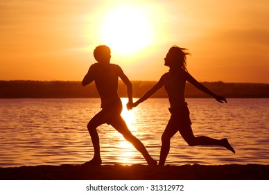 Silhouettes of happy couple running down seashore at sunset