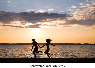 Silhouettes of happy couple running on seashore during summer vacations