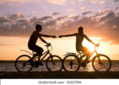Silhouettes of happy couple stretching arms to each other while riding bicycles on seashore at sunset