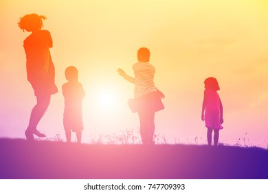 Silhouettes happy family playing at sunset.