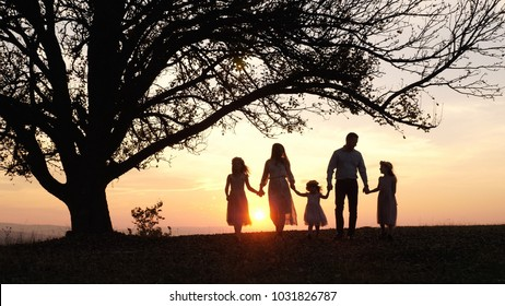 Silhouettes of happy family walking in the meadow near a big tree during sunset. Family spent time together. Enjoing each other