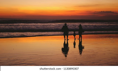 Silhouettes of happy family walking on sea coast during beautiful sunset