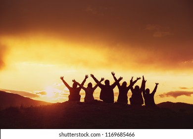 Silhouettes of happy friends with raised arms against sunset mountains