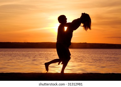 Silhouettes of happy guy holding his girlfriend and having fun at sunset