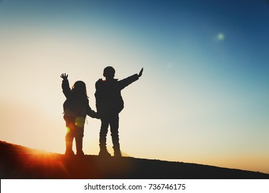 Silhouettes of happy little boy and girl hiking in sunset