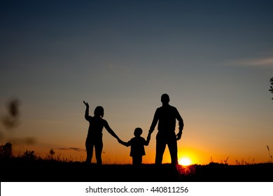 Silhouettes of happy parents having good time with their little children on the  sunset