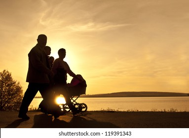 Silhouettes of happy parents - husband wife grandfather grandmother walking with stroller on the seacoast