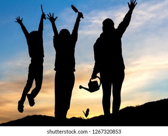 Silhouettes of happy people group with raised hands. before them watering young baby plants growing in germination sequence on fertile soil at sunset background