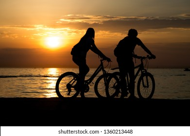 Silhouettes of happy sporty couple on bicycles on seashore at sunset .