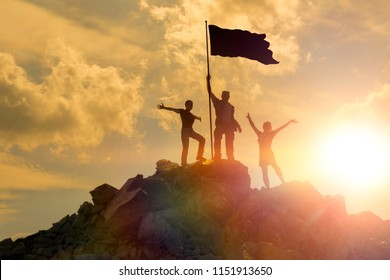 Silhouettes of happy three people on top of a mountain with the flag of victory. Success and achievements, Business, work in a team, and cooperation.