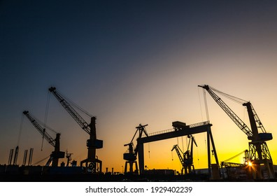Silhouettes of harbor cranes at sunset. Shipyard at sunset.