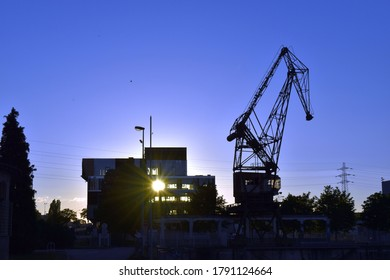Silhouettes of hoisting crane and building in process of construction with ray of sun passing through its window on background of sunset. Colorful image of housebuilding and construction process