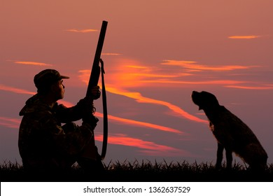 silhouettes of a hunter and a dog who are sitting at sunset background on the hunting