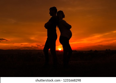 Silhouettes of husband and pregnant wife having conflict while they standing outdoor.Toned image.