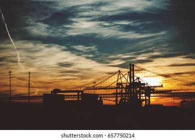 """Silhouettes of industrial and port zone near famous rope bridge """"Ponte 25 de Abril"""" in Lisbon, Portugal during stunning sunset and teal evening sky with clouds and traces from airplanes"""