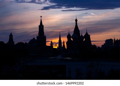 Silhouettes of Kremlin towers and domes of St. Basil's Cathedral on a background of bright sunset sky