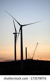 Silhouettes of large power generating windmills under construction, taken at sunset.