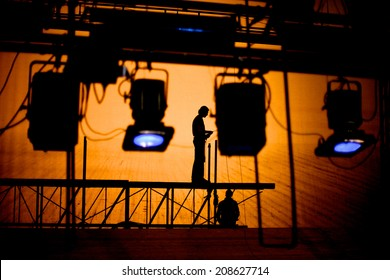 Silhouettes of lightening technicians standing on a scaffold regulating illumination of the stage