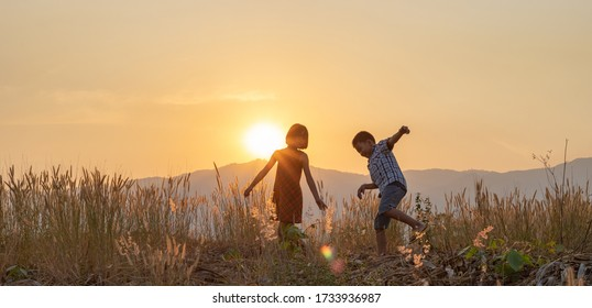 Silhouettes of little boy and girl playing on mountain meadow at sunset