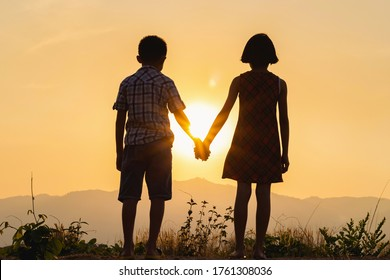 Silhouettes of little boy and girl standing on mountain at sunset
