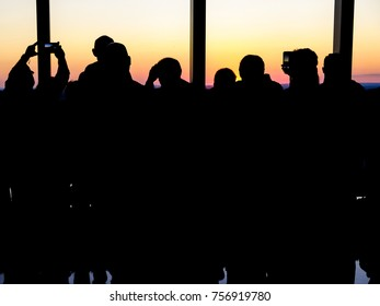 Silhouettes looking on a sunset, taking photos in a building.