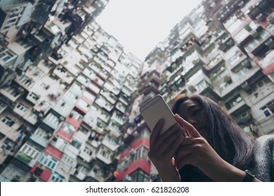 Silhouettes and low angle image of a woman using mobile phone with a crowded residential building in community in Quarry Bay, Hong Kong background