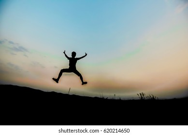 silhouettes; a man jumping in the sky