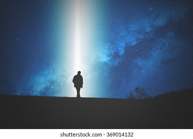 Silhouettes of a man on the top of the hill watching the stars. Stars are digital illustration, image only include elements of my work.