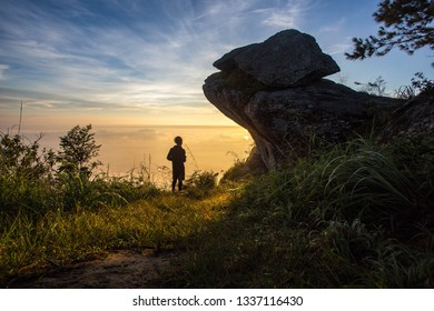 Silhouettes of man standing on top mountain and looking sunset.