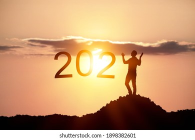 Silhouettes of the man standing on the top of mountain like as 1 text for 2021, victory concept.