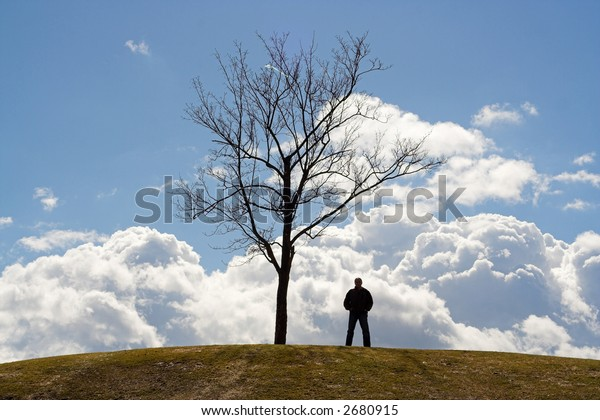 Silhouettes of man and tree on cloudy background