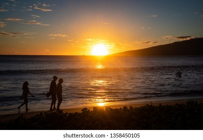 Silhouettes of a man, woman and daughter with cell phone walking on Sugar Beach in Maui, Hawaii at sunset, with a boogie boarder waiting for a wave.