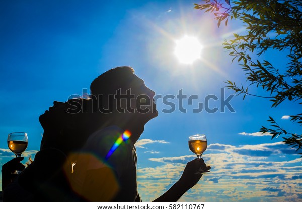Silhouettes of Man and woman drink glasses of champagne wine at sunset dramatic yellow sky with clouds background. Empty Copy space for inscription. Couple against sun shine rays