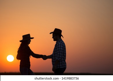 Silhouettes of man and woman farmers with hats shaking hands in field during sunset