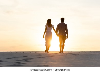 silhouettes of man and woman holding hands while walking on beach against sun during sunset