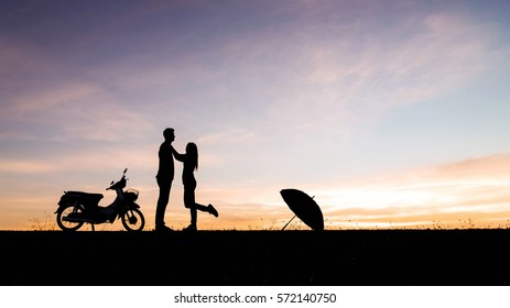 Silhouettes of man and woman in love at sunset