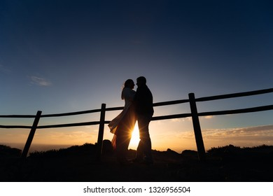 silhouettes of a man and a woman near the fence. They are hugged near the fence on the background of the sunset and the ocean
