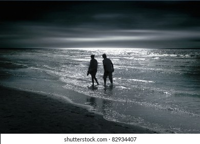 Silhouettes of the man and the woman on the sea. Sea at night with moonlight reflecting.