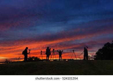 Silhouettes of many photographers. Beautiful sky and sunrise.