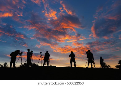 Silhouettes of many photographers. Beautiful sky and sunrise.