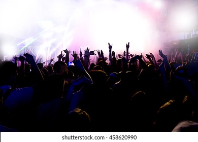 silhouettes of a massive crowd at the party concert club music happy
