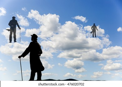 silhouettes of men with a cane and bowl hat climbing up the clouds in the sky