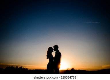 silhouettes of men and women in love at sunset