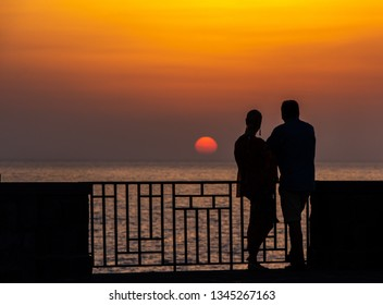Silhouettes of men and women watching the sunset on the sea.