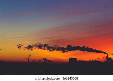 Silhouettes of modern buildings, architecture and smoke from the chimneys at background of a colorful sunset. Cityscape. Toned image with copy space