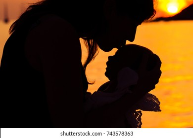 Silhouettes of mom and newborn on a sunset